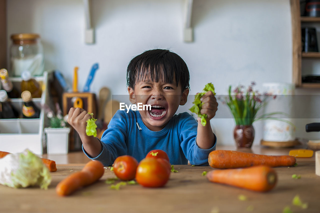 childhood, child, boys, males, food and drink, food, men, front view, healthy eating, portrait, one person, real people, indoors, home interior, freshness, domestic room, lifestyles, home, wellbeing, casual clothing, innocence, mouth open