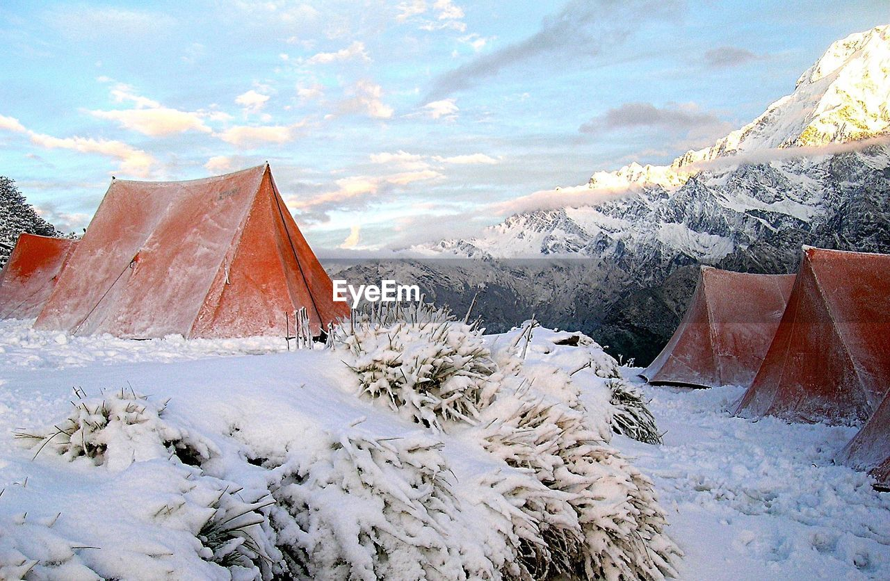 Tents On Snow Covered Field Against Sky