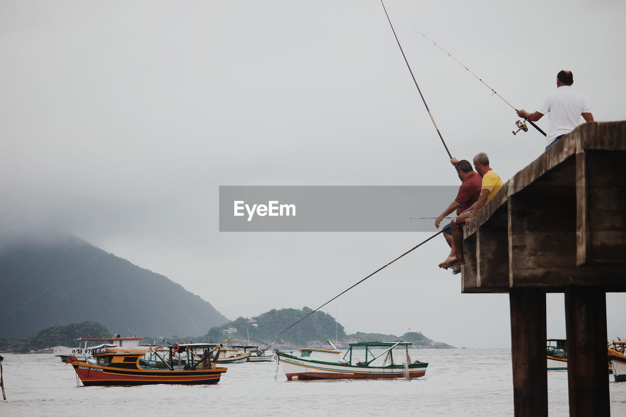 water, transportation, mode of transportation, nautical vessel, sky, sea, nature, day, real people, mountain, waterfront, beauty in nature, travel, men, scenics - nature, architecture, occupation, built structure, outdoors, fisherman, fishing industry