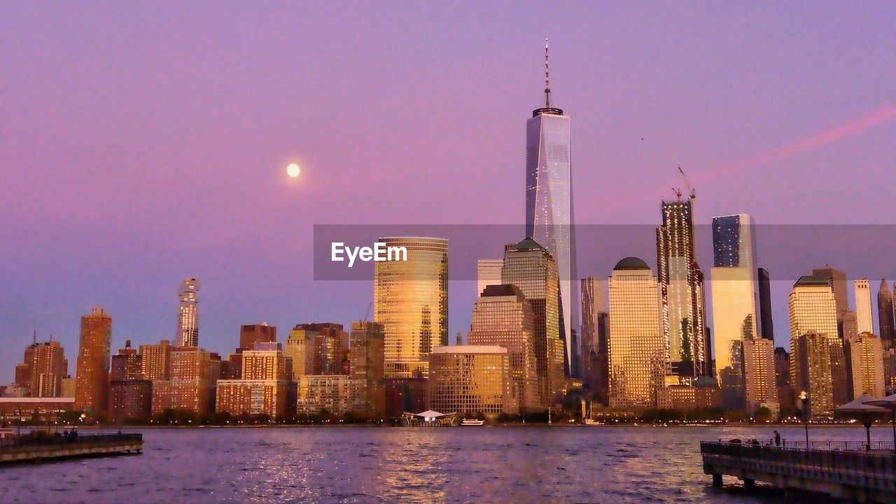 architecture, building exterior, skyscraper, built structure, city, tall - high, tower, travel destinations, urban skyline, modern, illuminated, financial district, sky, water, cityscape, river, waterfront, outdoors, no people, downtown district, night, moon, sunset, nature