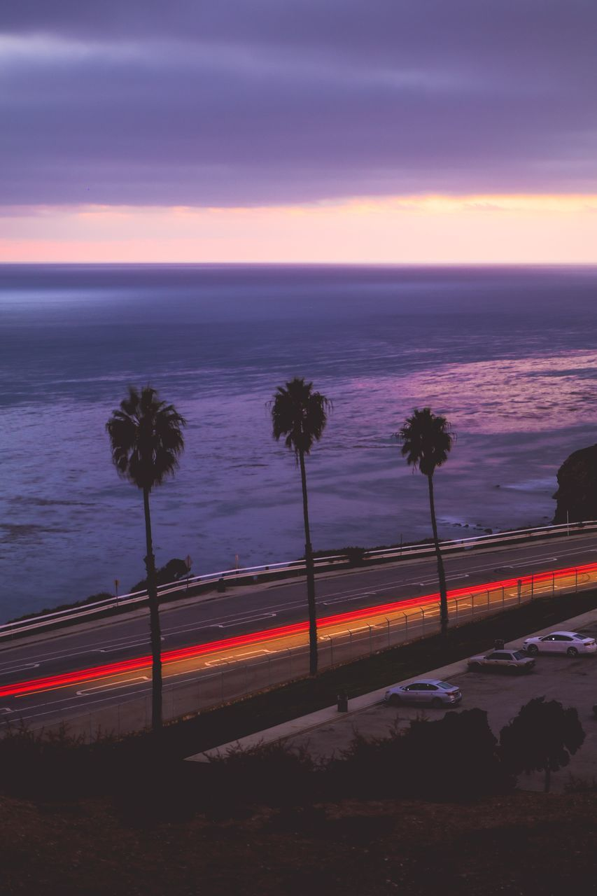 sky, horizon over water, sea, sunset, transportation, scenics - nature, beauty in nature, horizon, cloud - sky, road, long exposure, nature, light trail, motion, water, no people, orange color, night, mode of transportation, outdoors