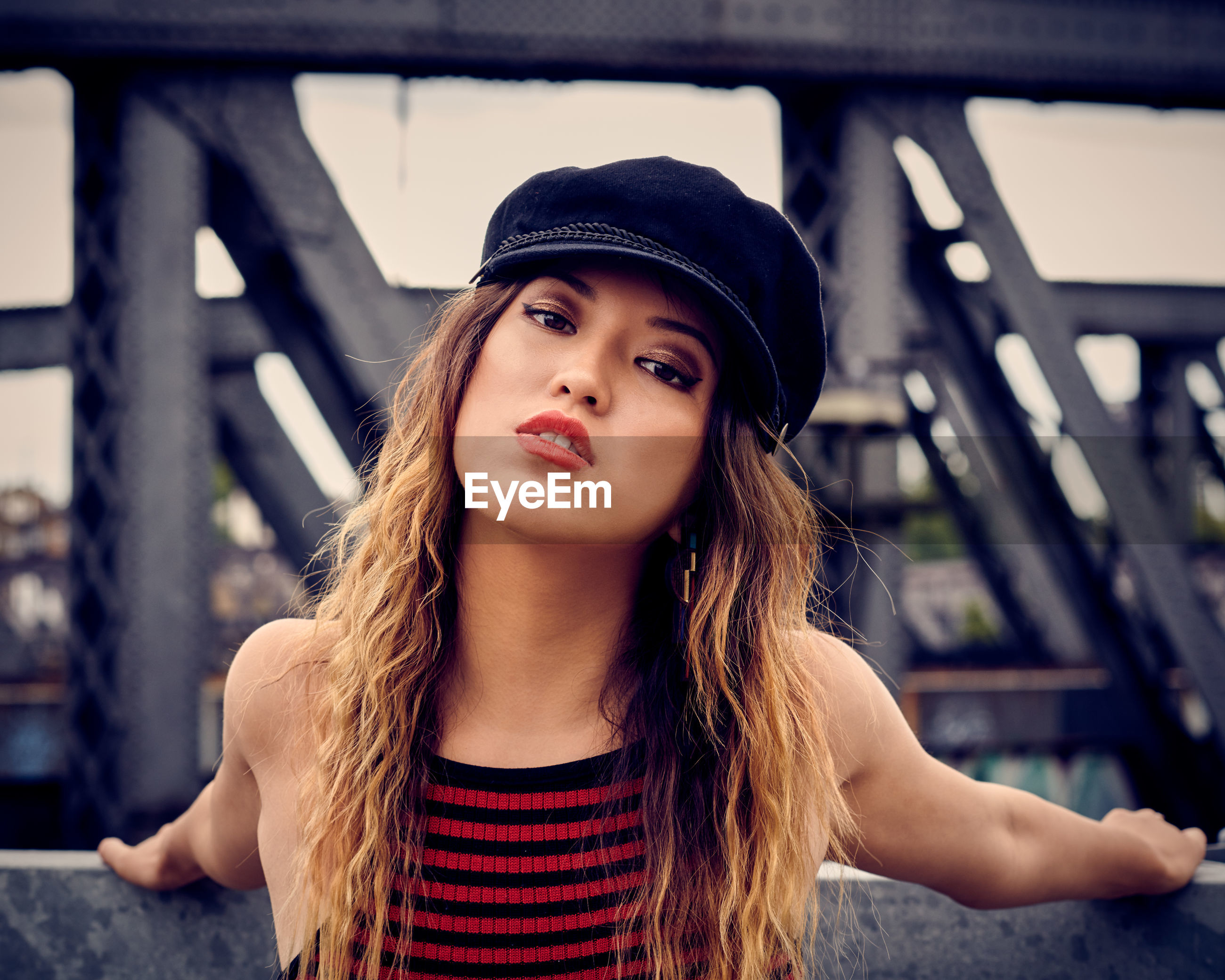 Portrait of beautiful young woman wearing flat cap against built structure