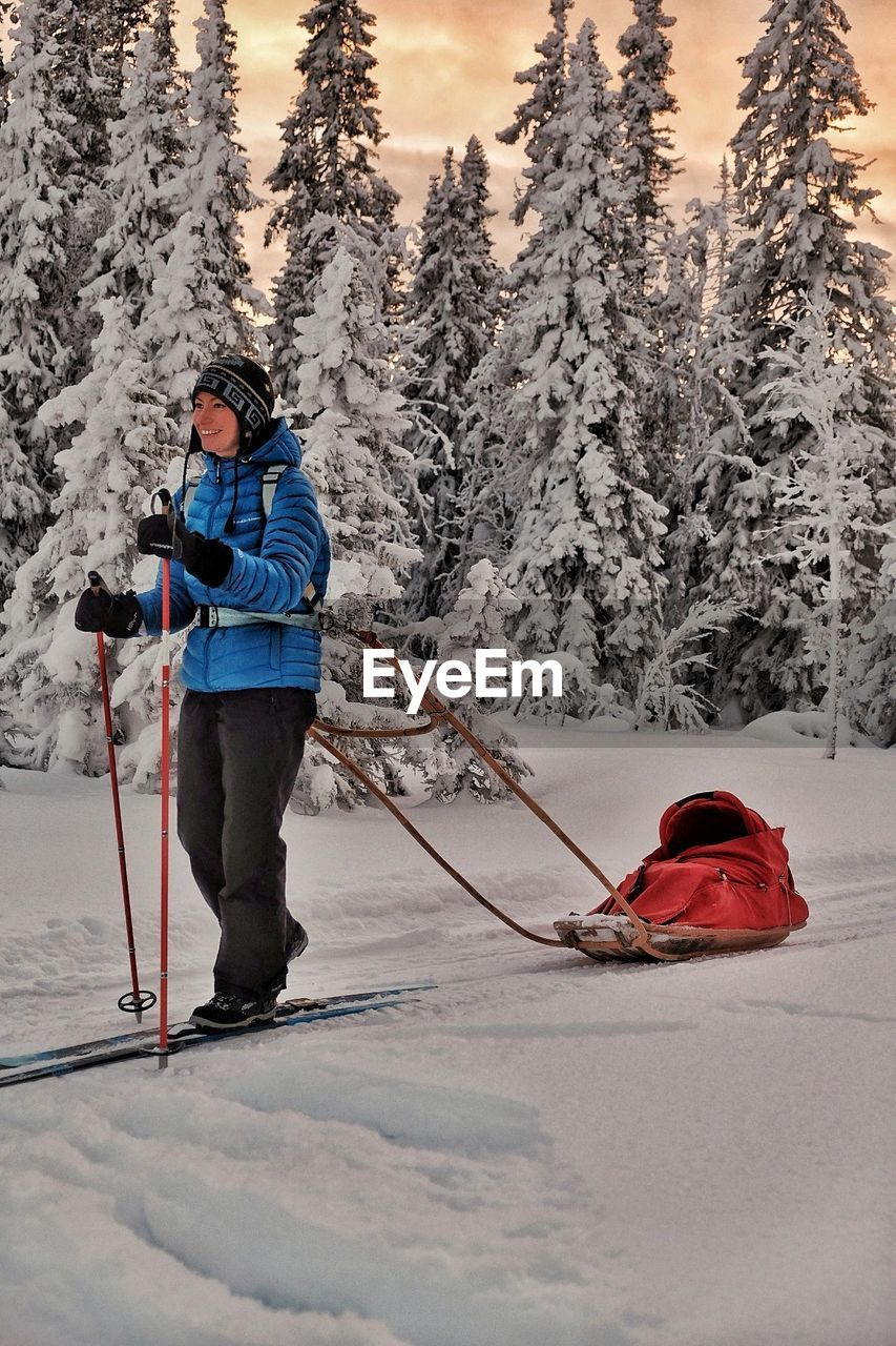 Full Length Of Woman Skiing With Sled On Snow Covered Land