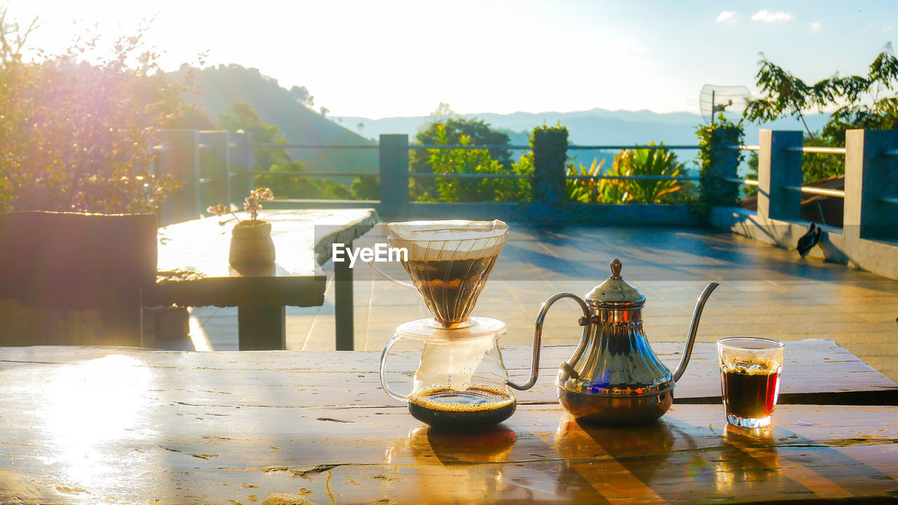 table, sunlight, refreshment, food and drink, drink, nature, day, glass, sky, freshness, no people, food, still life, outdoors, drinking glass, plant, glass - material, household equipment, transparent, restaurant
