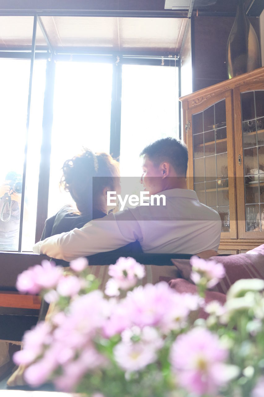 two people, window, real people, men, indoors, adult, flower, lifestyles, flowering plant, plant, togetherness, people, young adult, day, bonding, love, nature, males, leisure activity, young men, positive emotion, couple - relationship