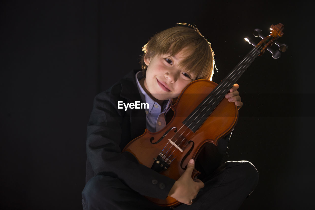 Boy holding violin while sitting against black background