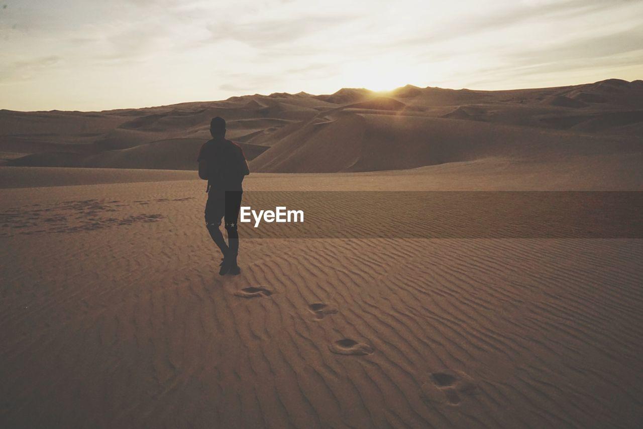 Rear view of man walking on desert against sky during sunset