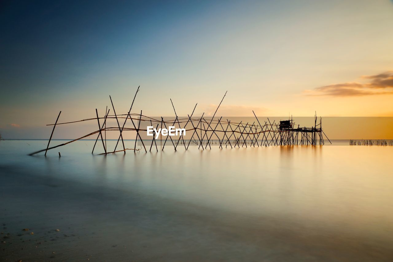 sky, water, sunset, scenics - nature, sea, beauty in nature, tranquility, tranquil scene, cloud - sky, reflection, waterfront, nature, no people, orange color, non-urban scene, idyllic, architecture, outdoors, built structure, horizon over water, fishing industry, wooden post