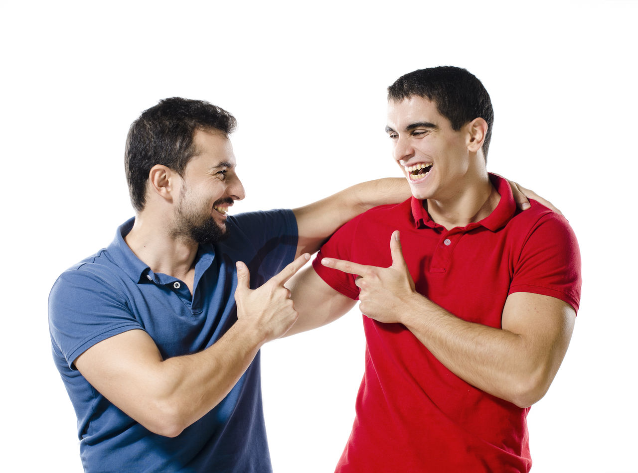 Smiling male friends pointing against white background