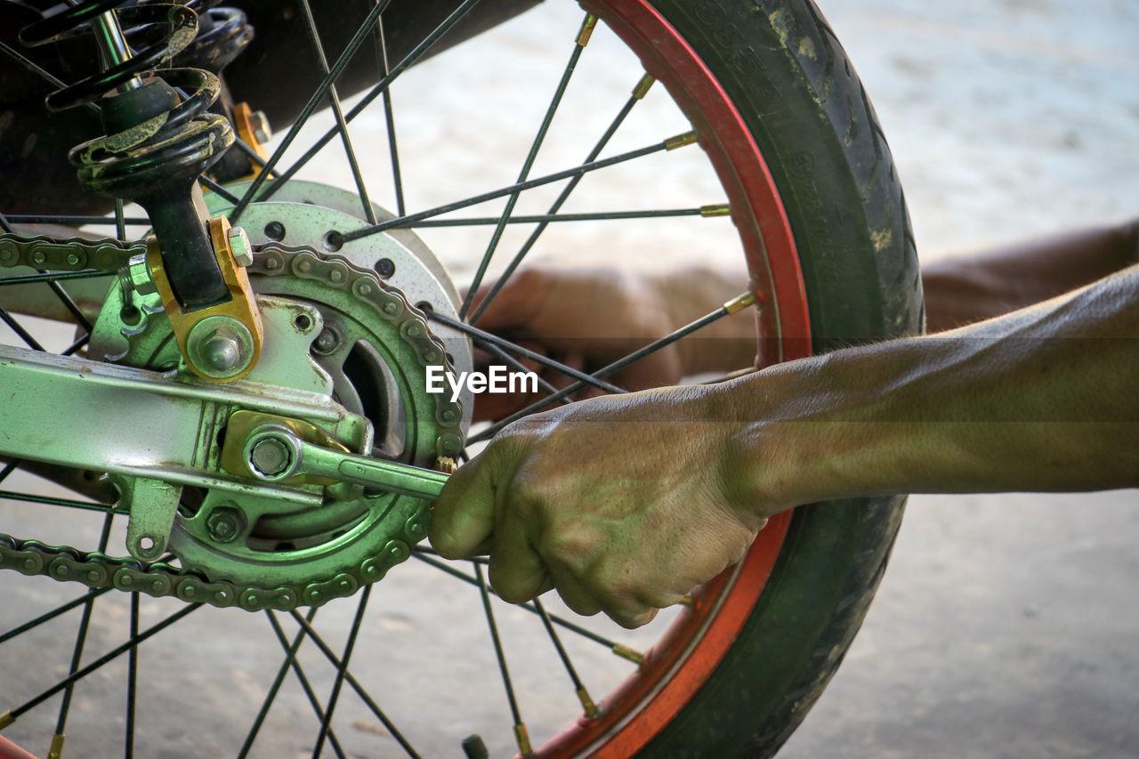 Cropped hand repairing wheel of motorcycle