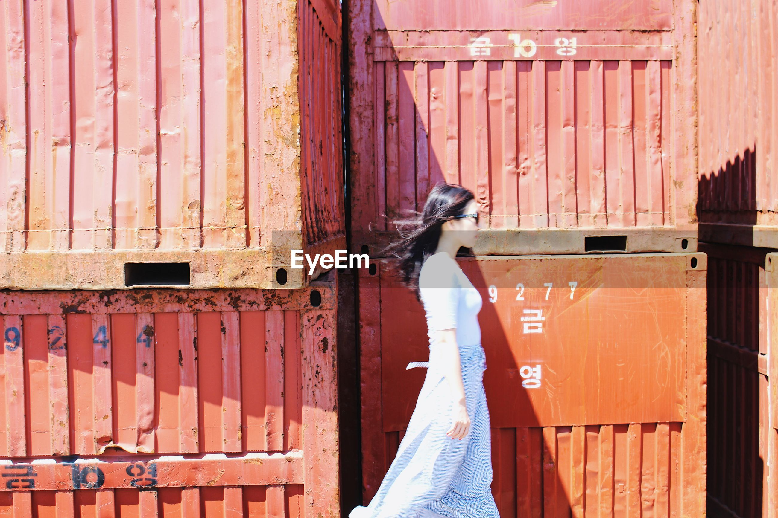 Side view of young woman walking by cargo containers