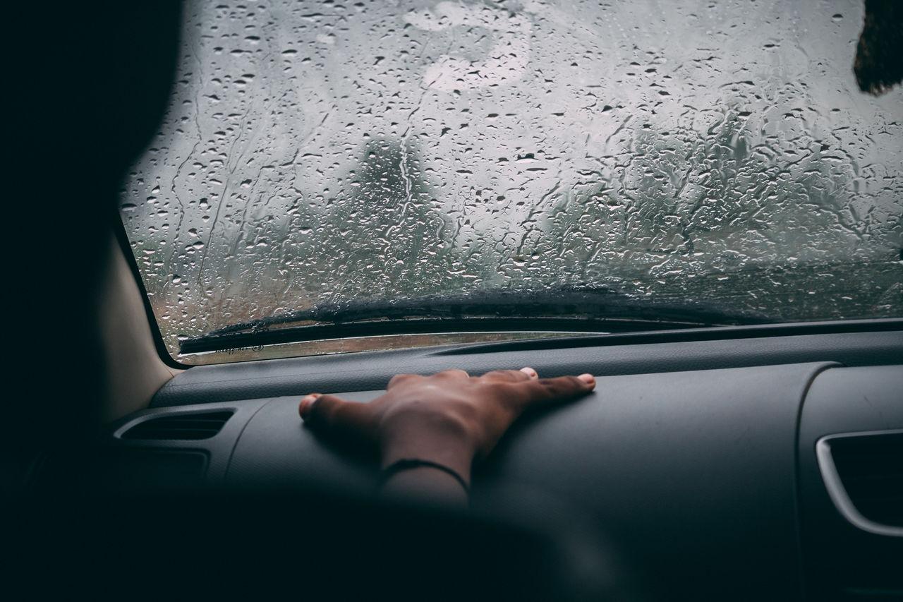 Cropped hand on car dashboard during rainy season