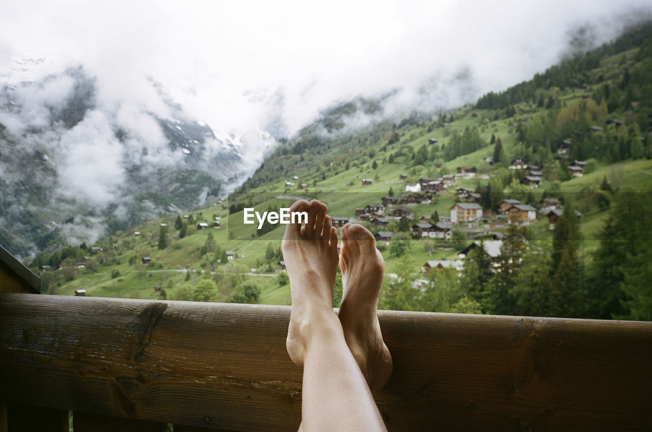 LOW SECTION OF WOMAN RELAXING ON MOUNTAINS