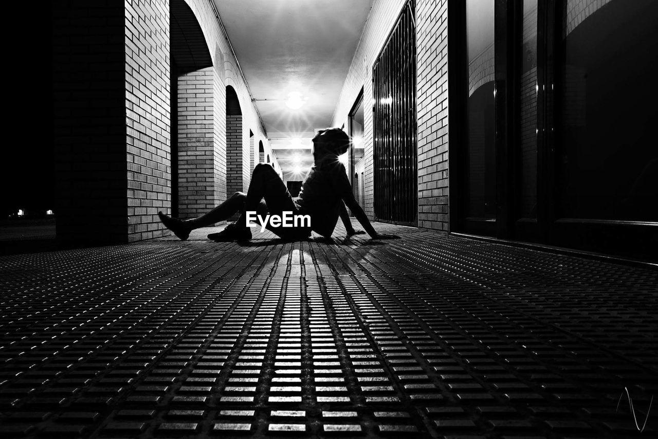 Full Length Of Man Sitting On Illuminated Corridor At Night