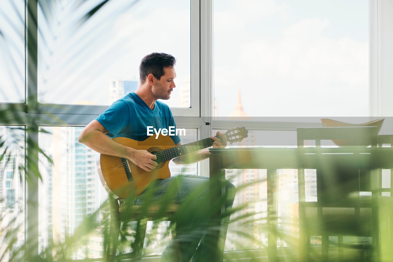 Man playing guitar sitting at home