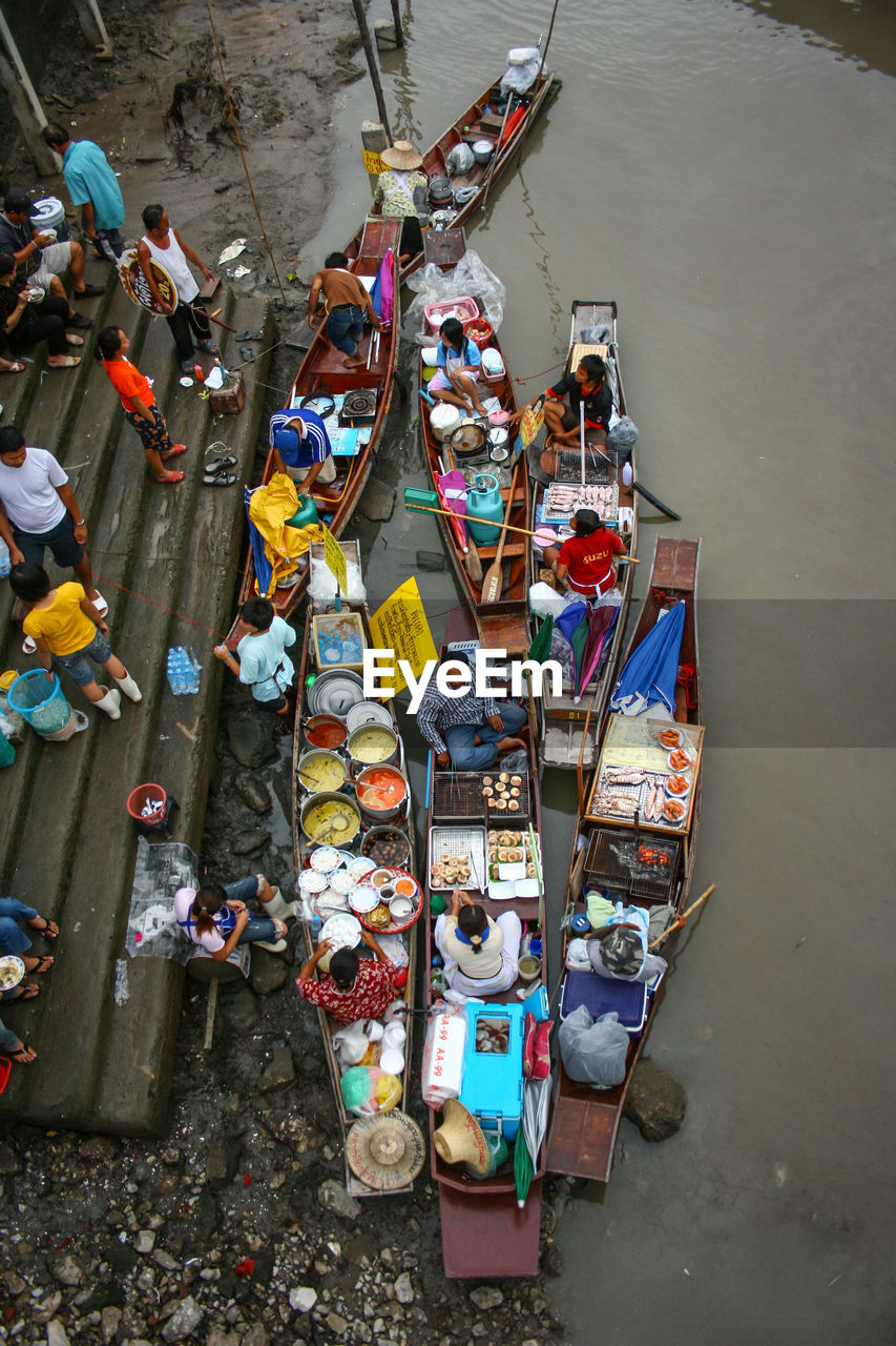 HIGH ANGLE VIEW OF PEOPLE IN BOAT AT RIVERBANK
