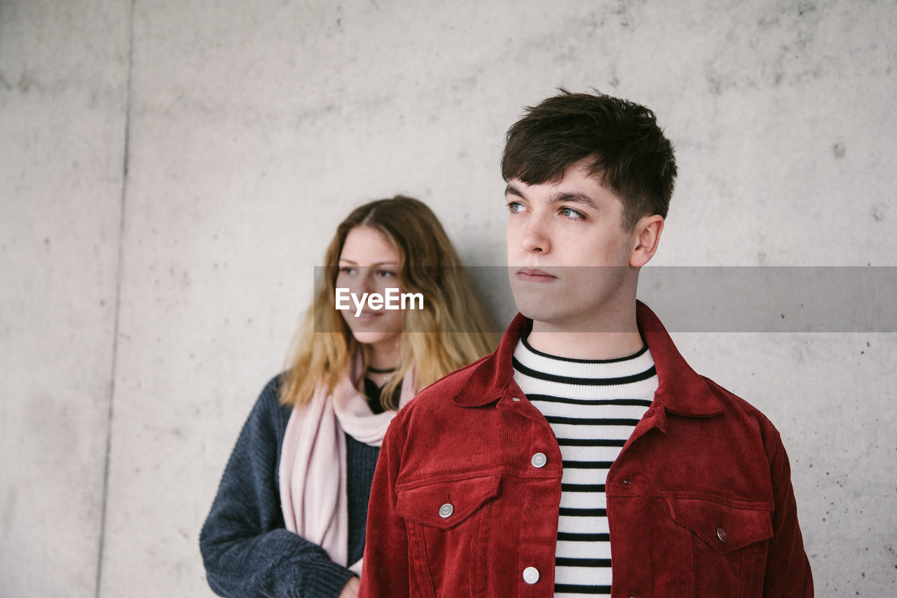 Young couple looking away while standing against wall
