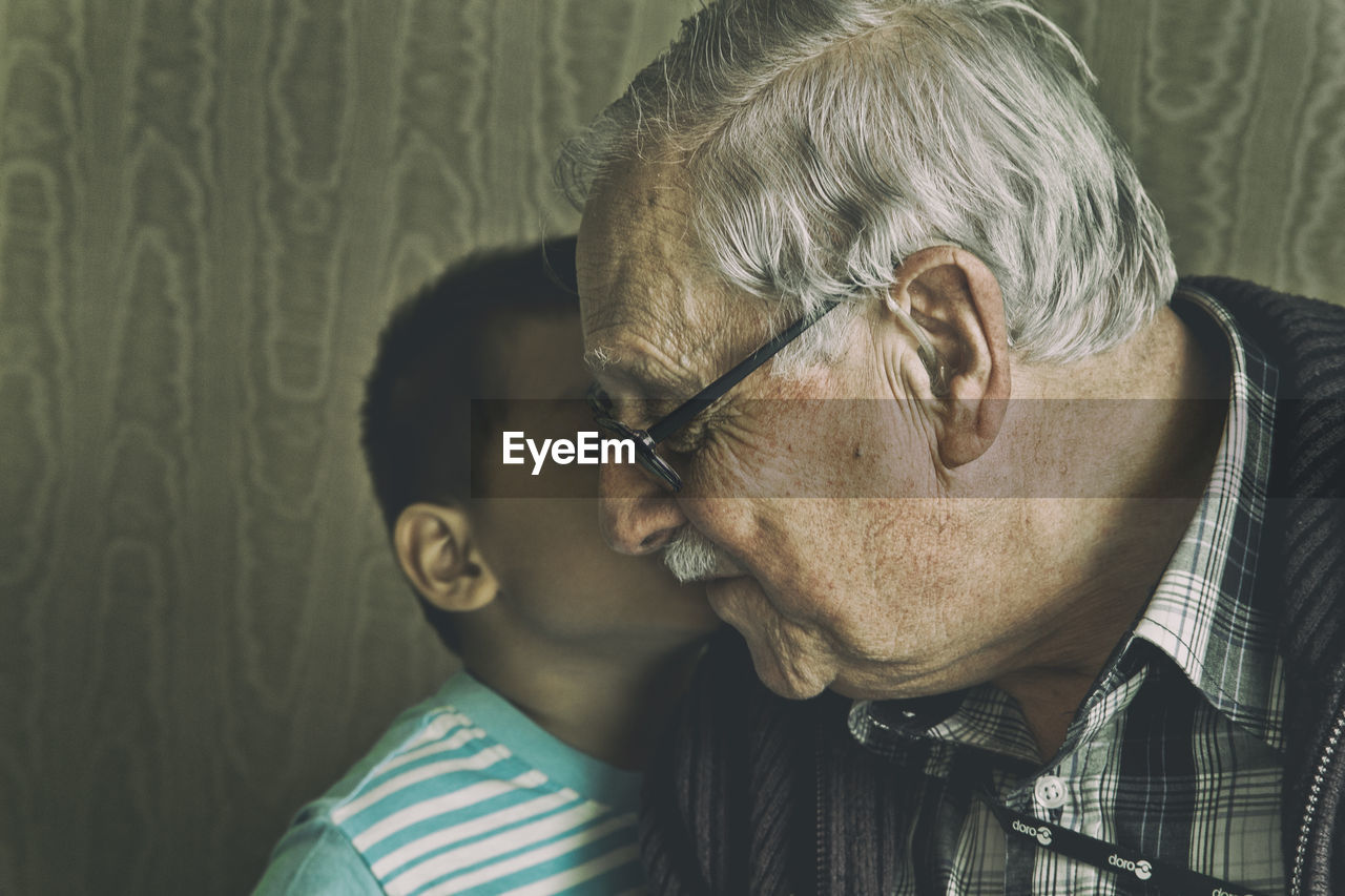Close-Up Of Grandfather And Grandson Against Wall At Home