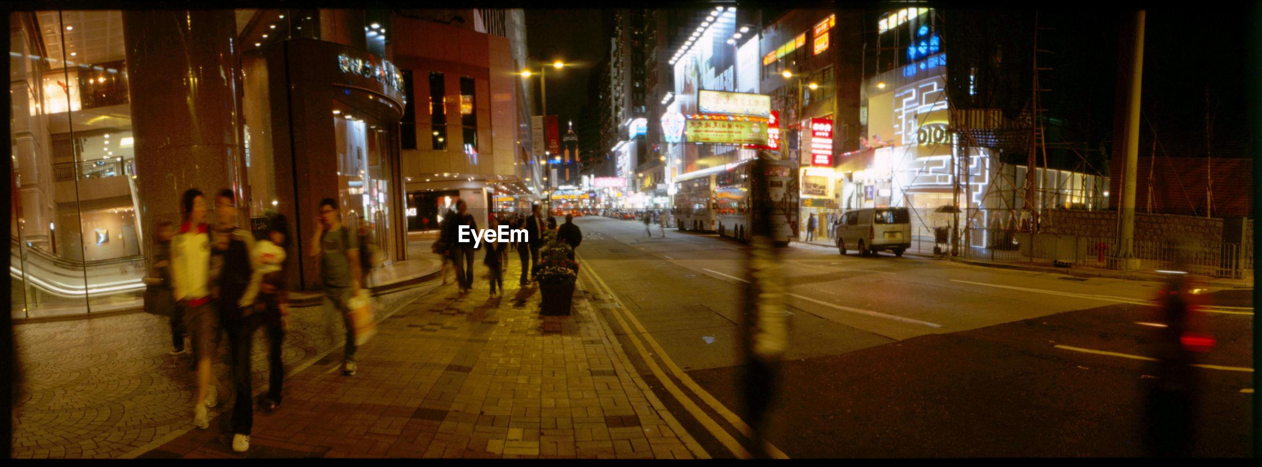 People on sidewalk by city street at night