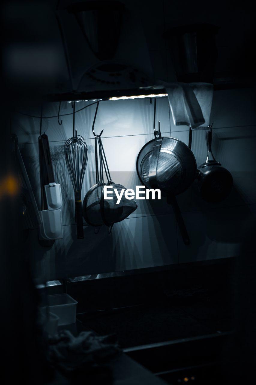 Close-up of kitchen utensils hanging at home in darkroom