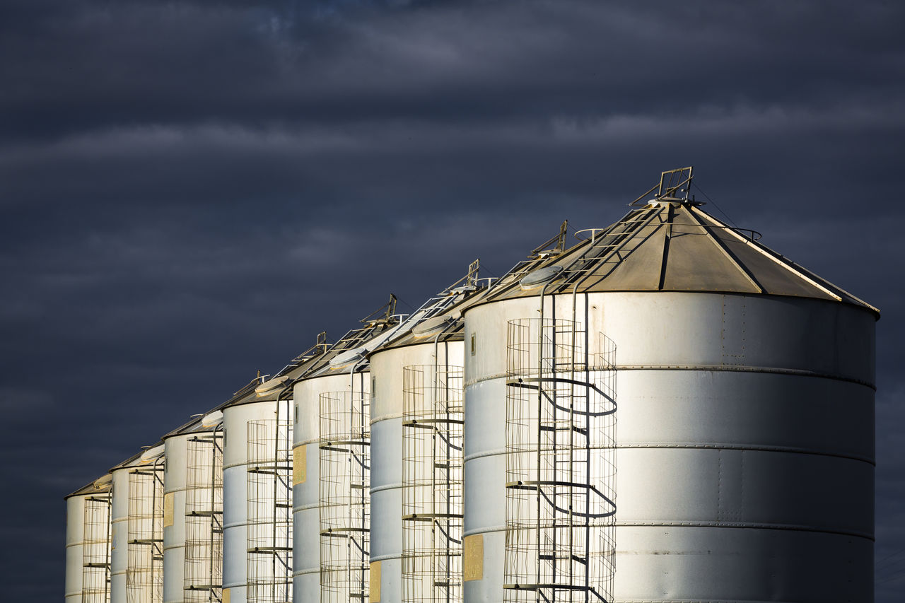 cloud - sky, sky, silo, industry, factory, nature, storage compartment, storage tank, metal, no people, outdoors, low angle view, overcast, agriculture, built structure, day, architecture, refinery, industrial building, silver colored