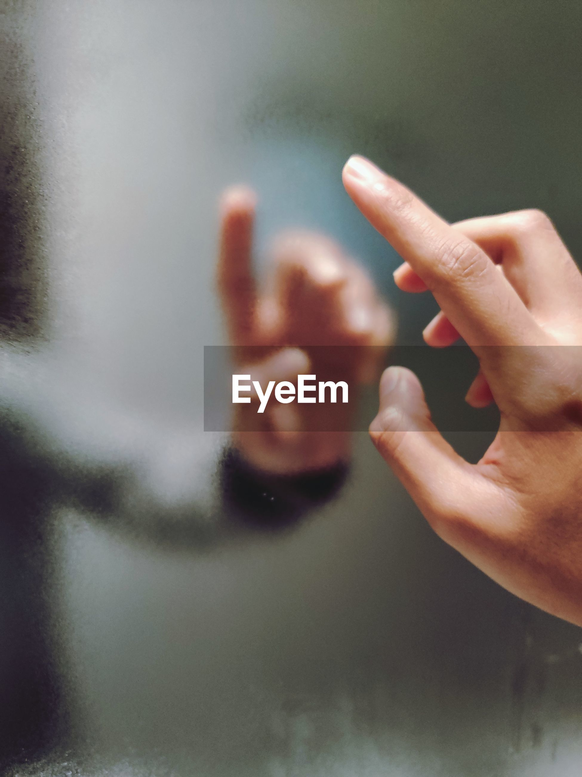 Close-up of human hand along it's blurred reflection