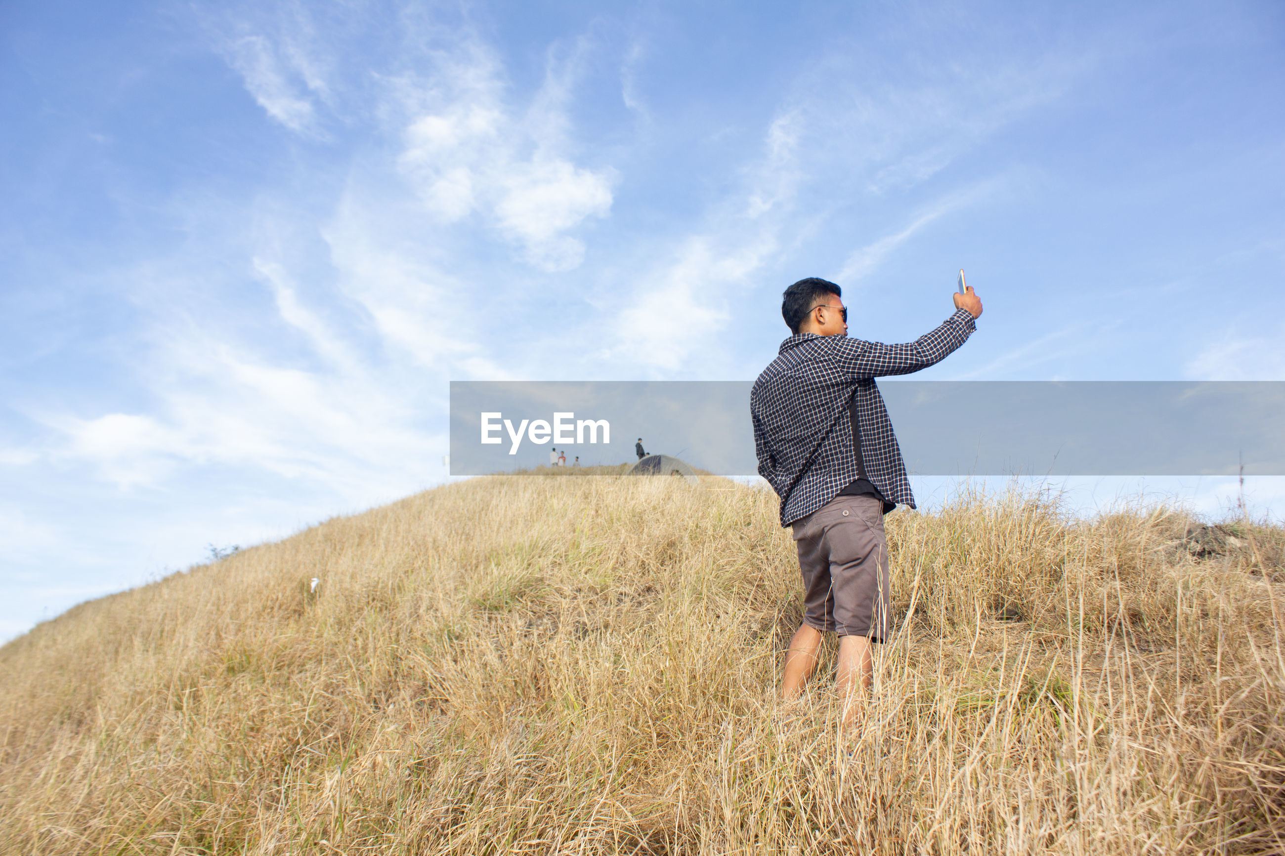 Young man taking selfie with mobile phone while standing on mountain against sky