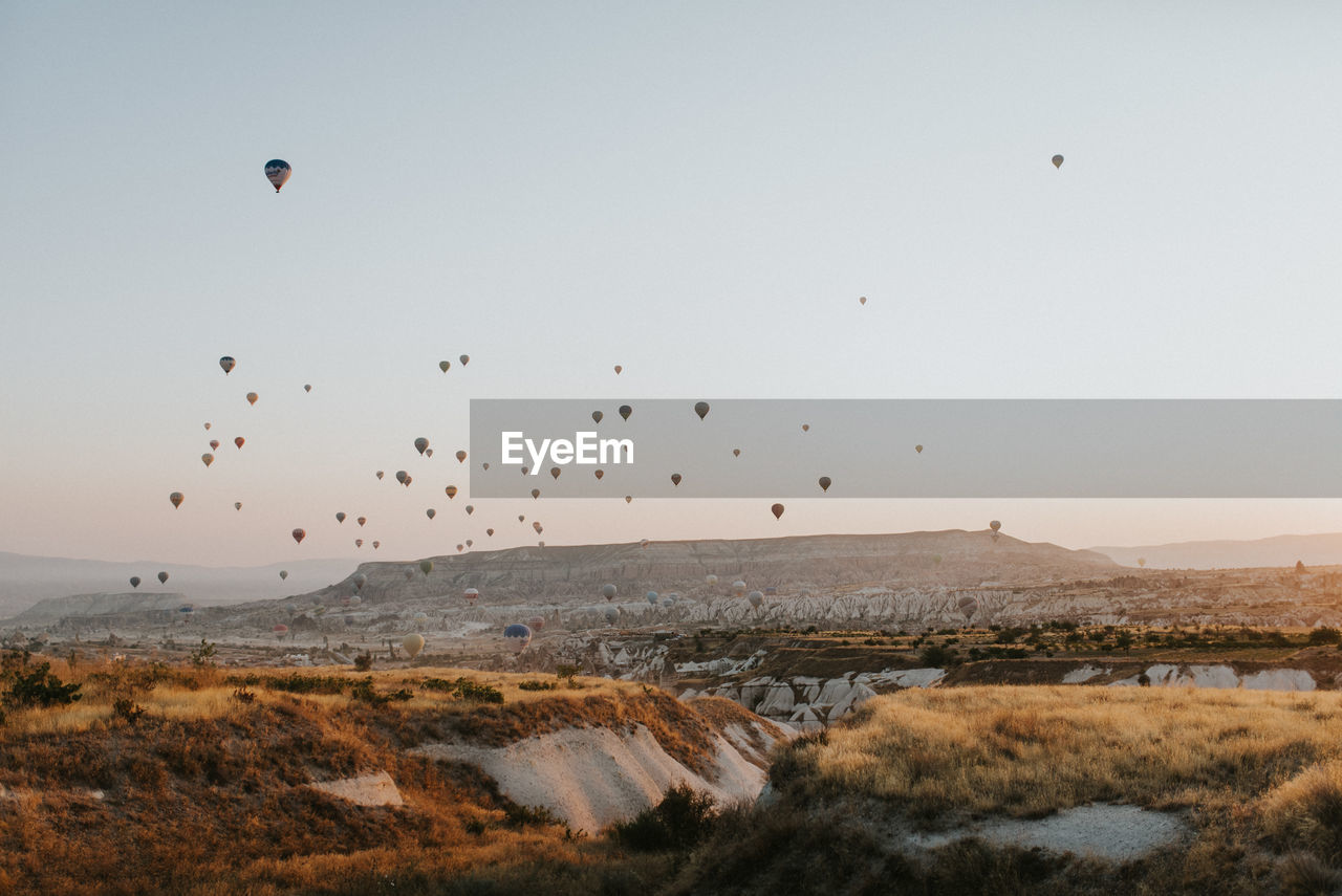Hot Air Balloons Flying Over Landscape Against Clear Sky