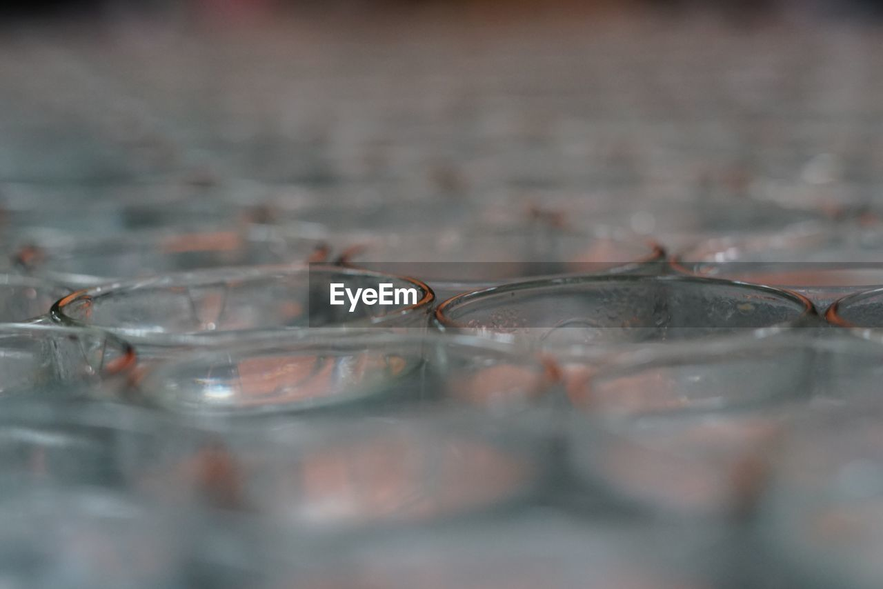 selective focus, glass - material, close-up, transparent, indoors, no people, glass, glasses, still life, table, household equipment, drinking glass, eyeglasses, food and drink, water, nature, group of objects, motion
