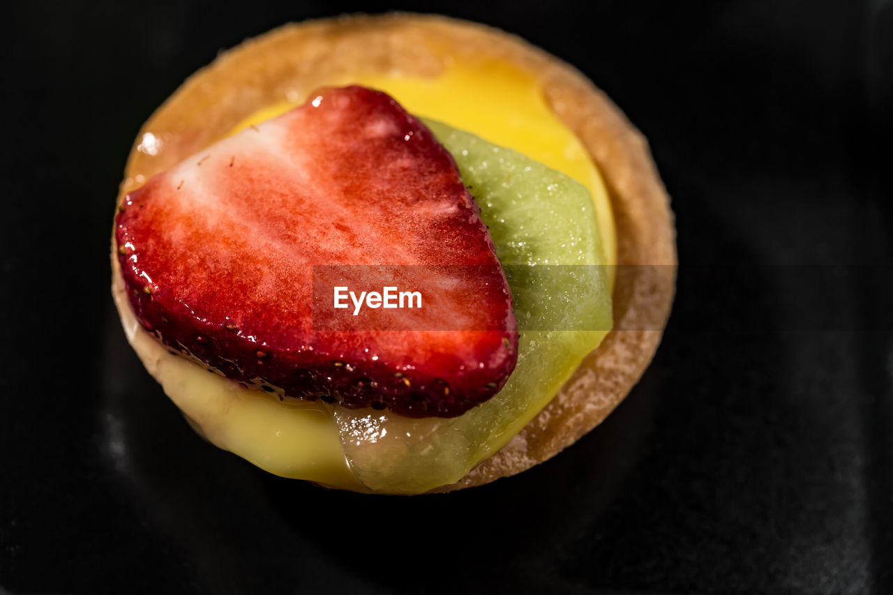food, food and drink, freshness, fruit, healthy eating, close-up, indoors, still life, wellbeing, no people, black background, slice, studio shot, ready-to-eat, table, strawberry, red, indulgence, cross section, apple - fruit, temptation