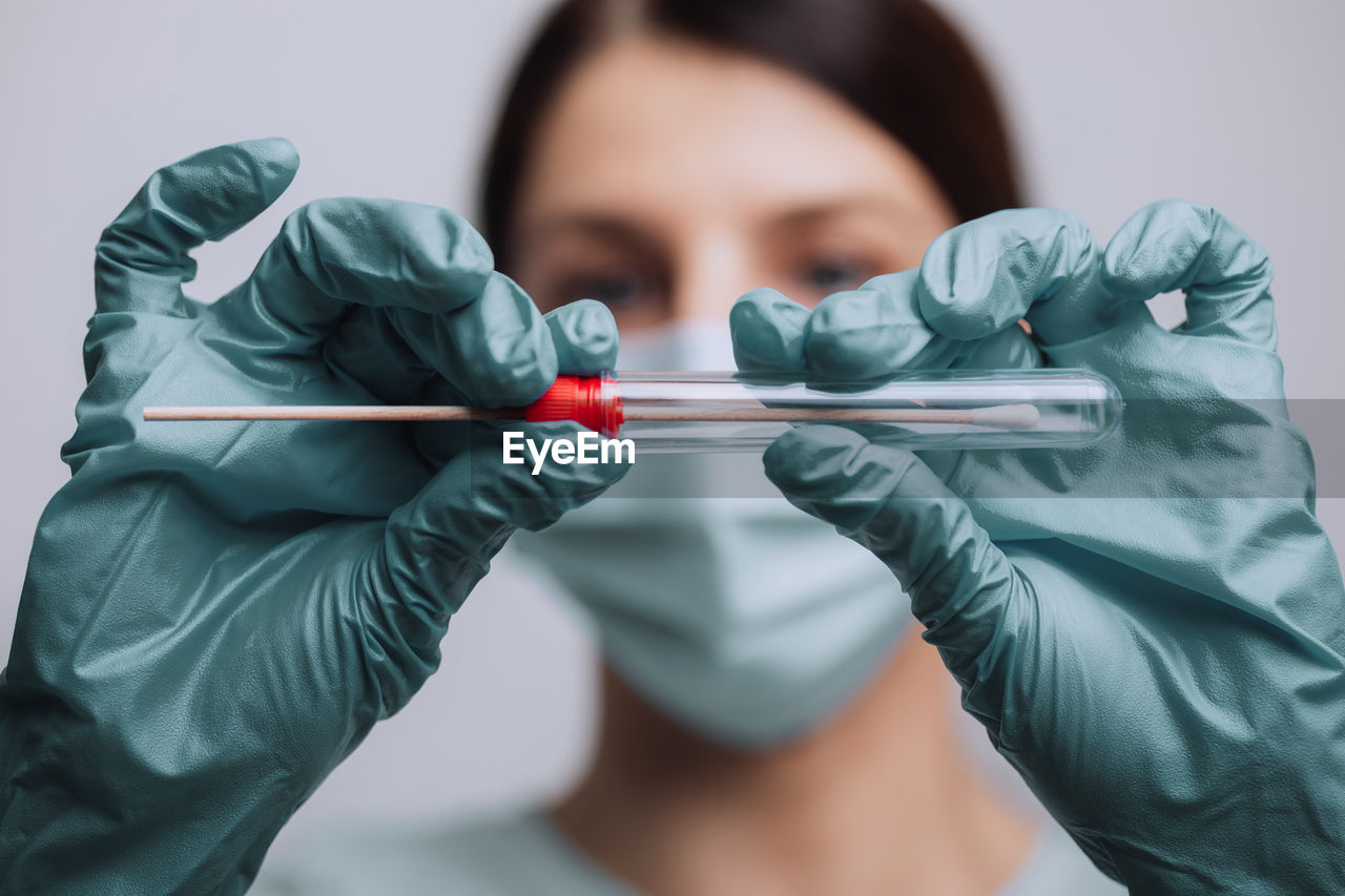 Close-up of doctor wearing mask holding test tube against gray background