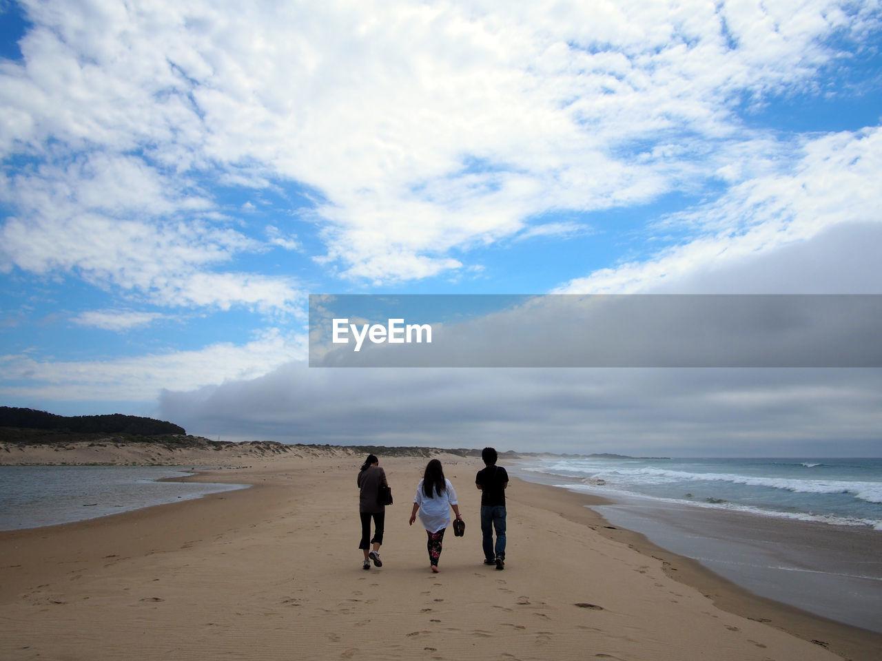 Rear view of people walking at beach against sky