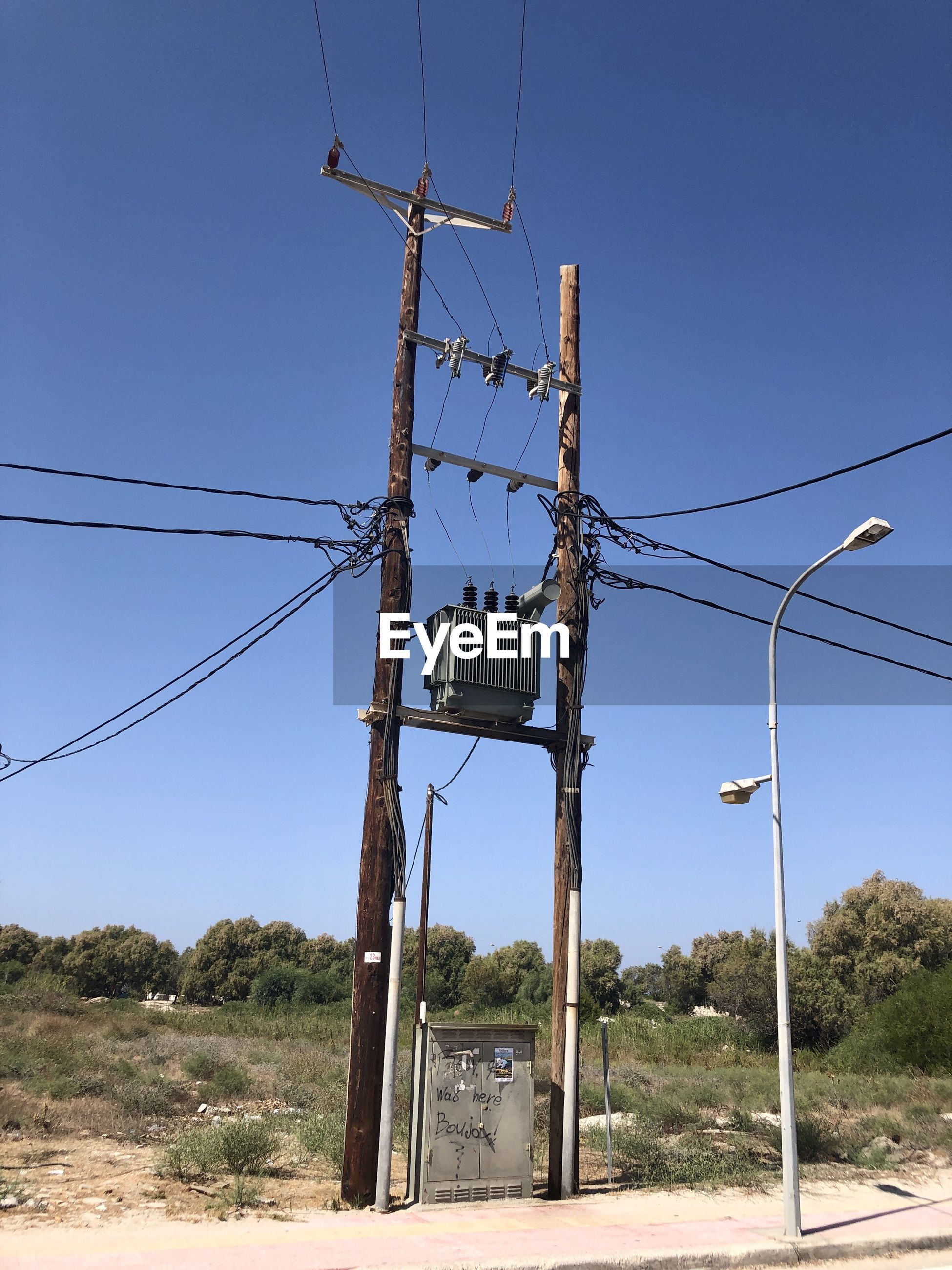LOW ANGLE VIEW OF ELECTRICITY PYLONS ON FIELD AGAINST CLEAR SKY
