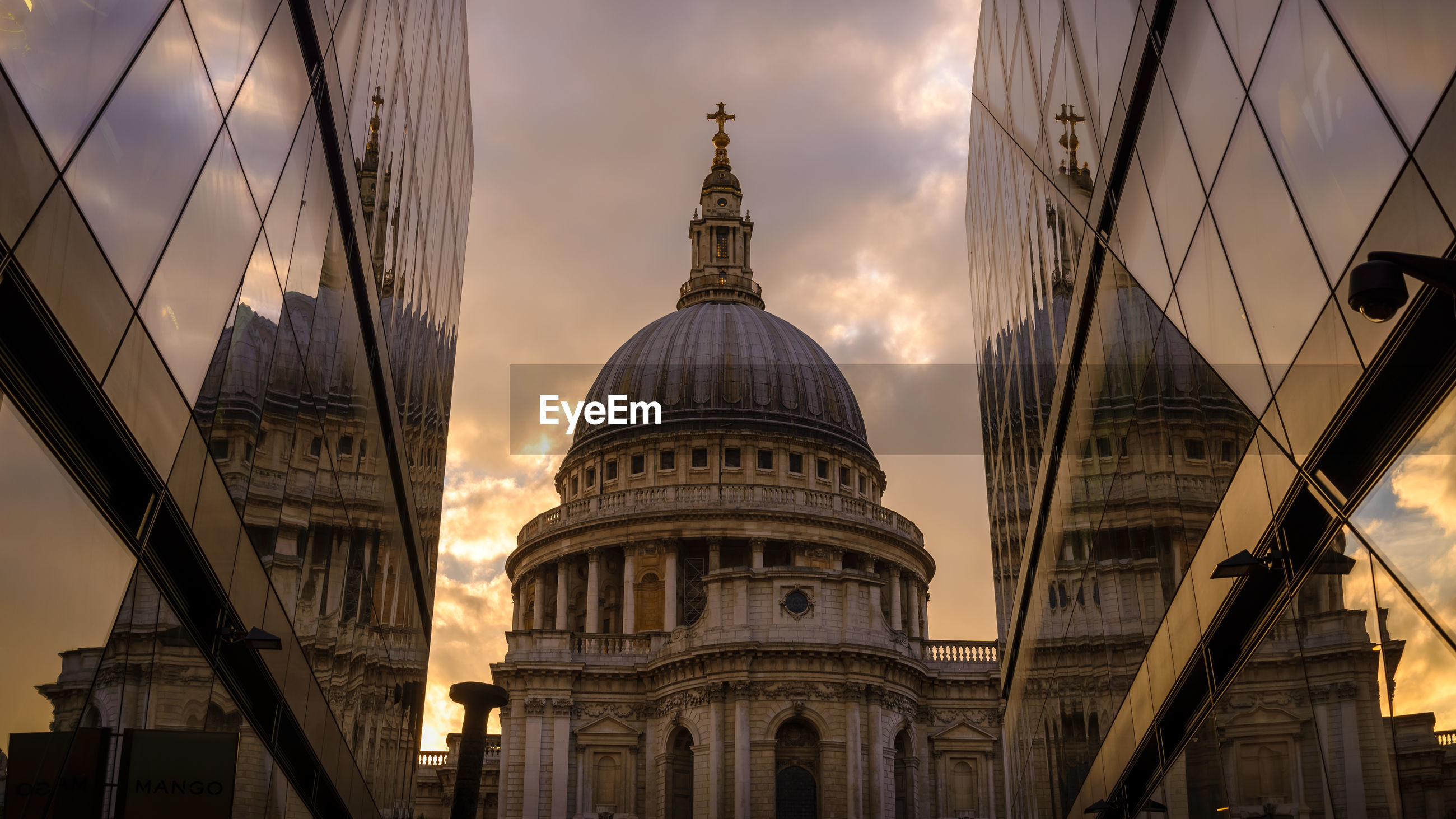 Low angle view of st paul cathedral reflecting on modern buildings during sunset