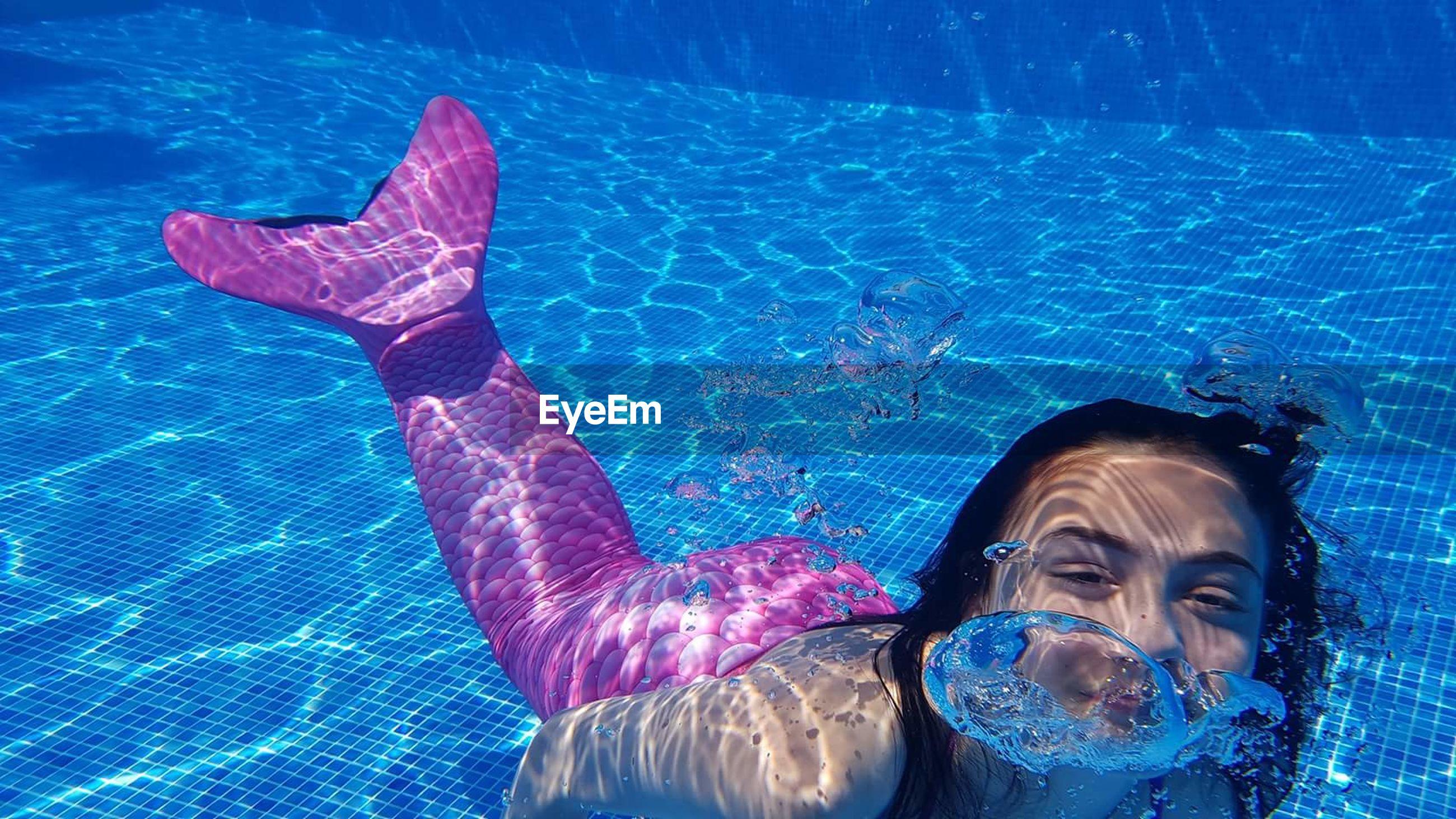 Girl dressed as mermaid in swimming pool