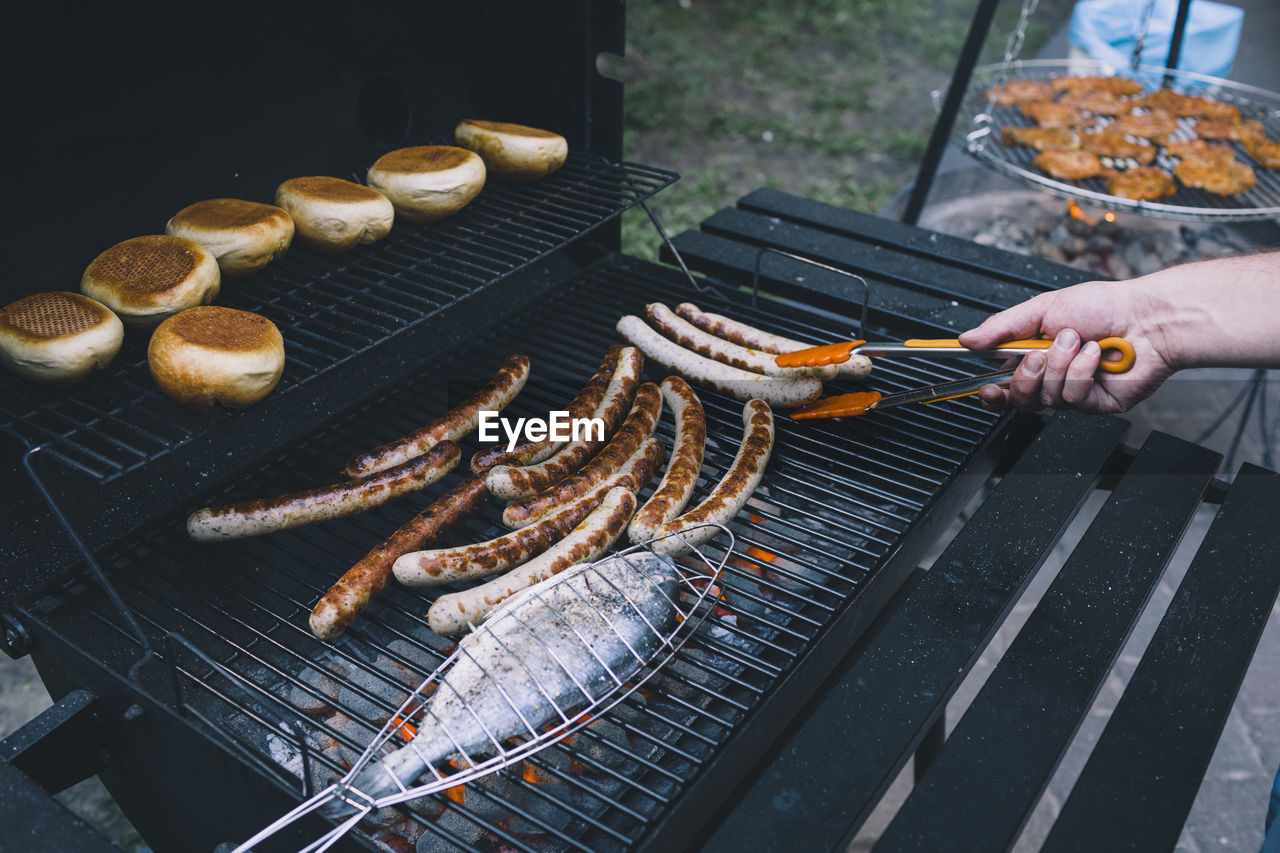 Close-Up Of Fish And Sausages On Barbecue Grill