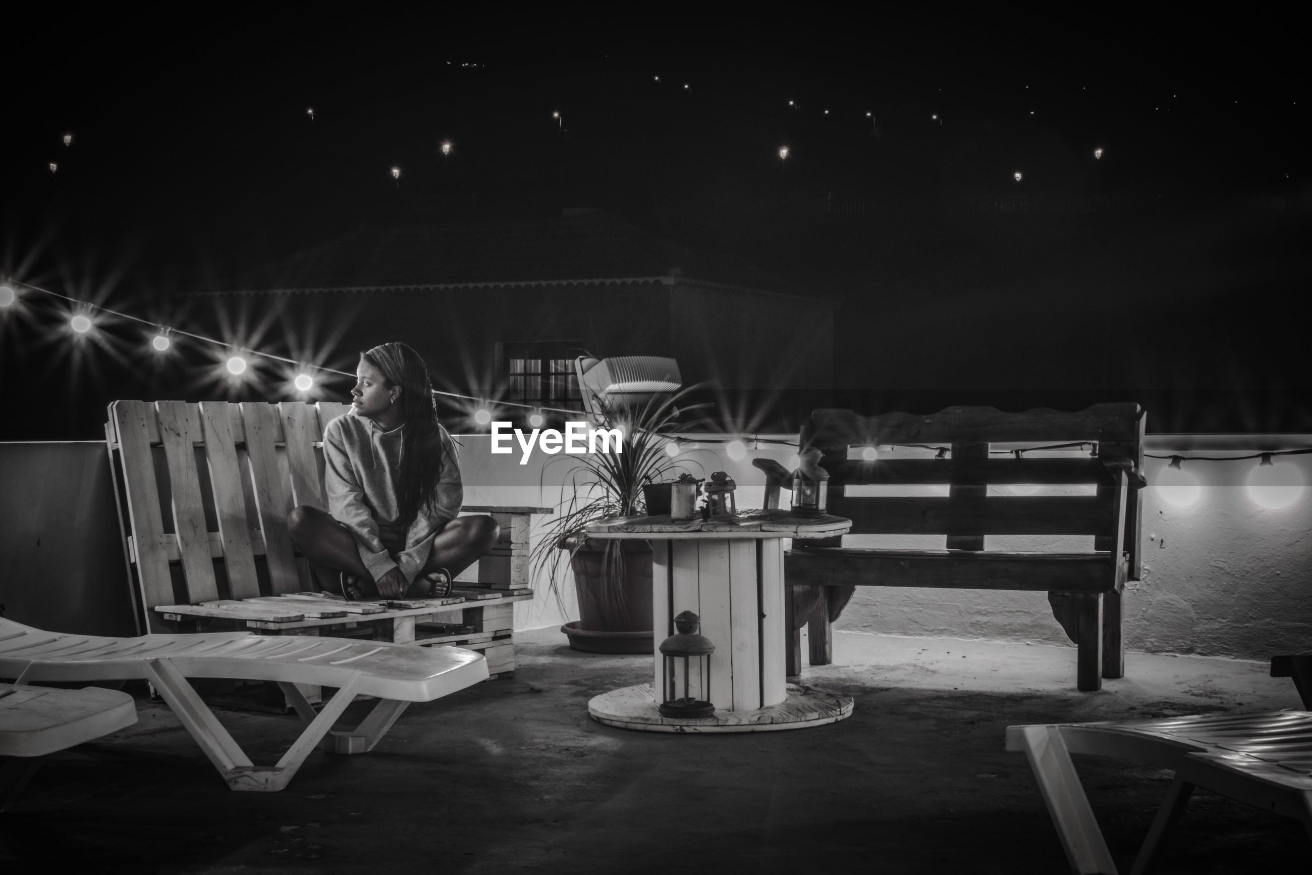 Woman sitting on bench against sky at night