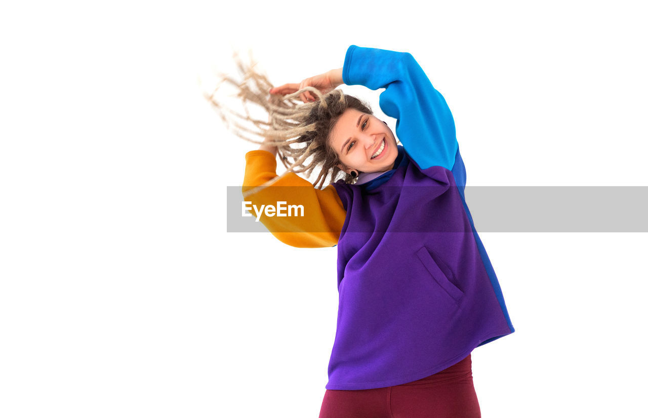 SMILING YOUNG WOMAN WITH ARMS RAISED AGAINST WHITE BACKGROUND