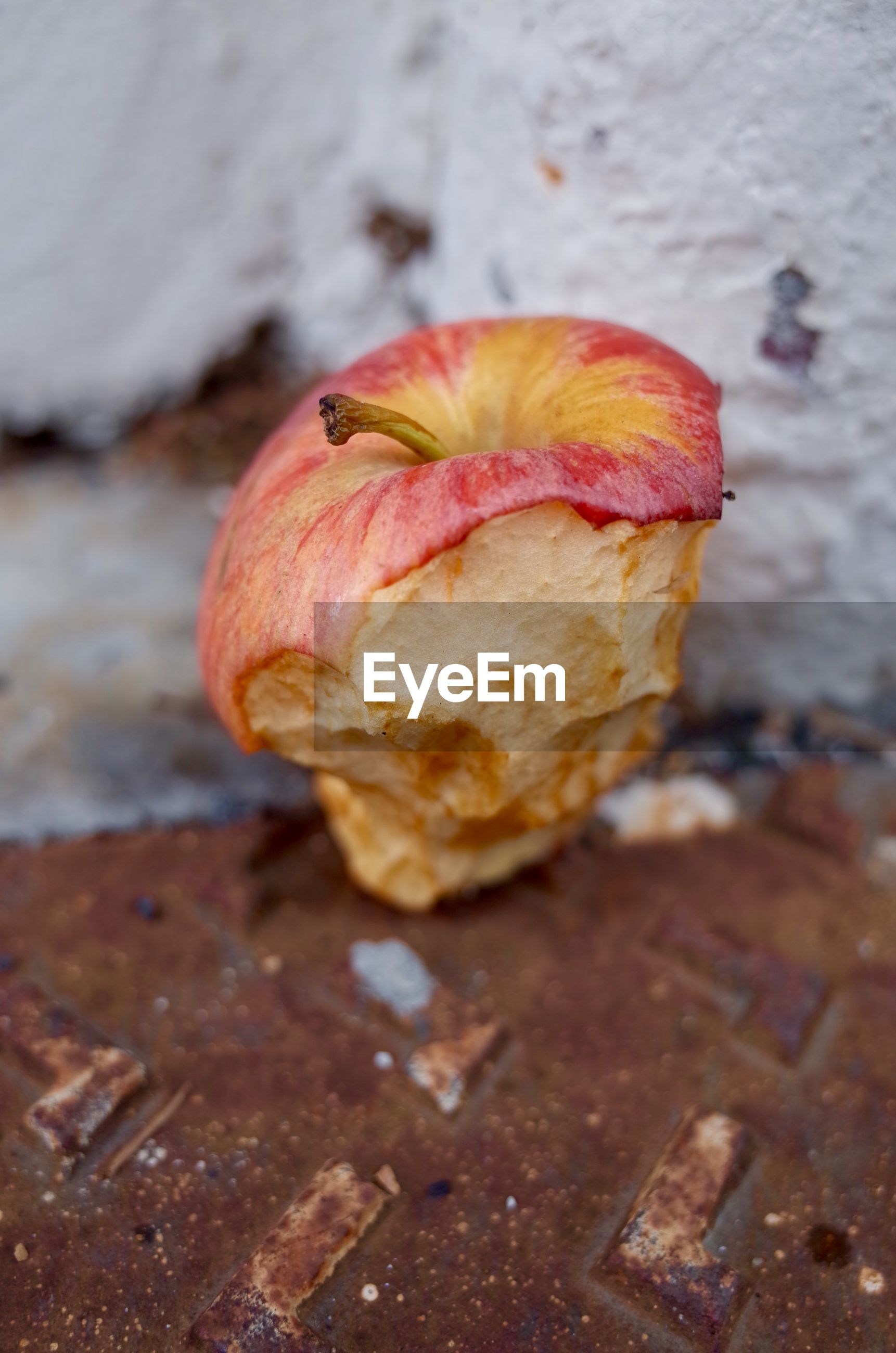 Close-up of eaten apple on rusty metal against wall