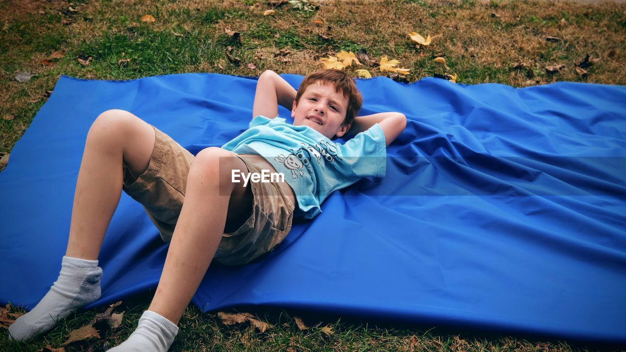 High angle view of boy lying on blanket at filed