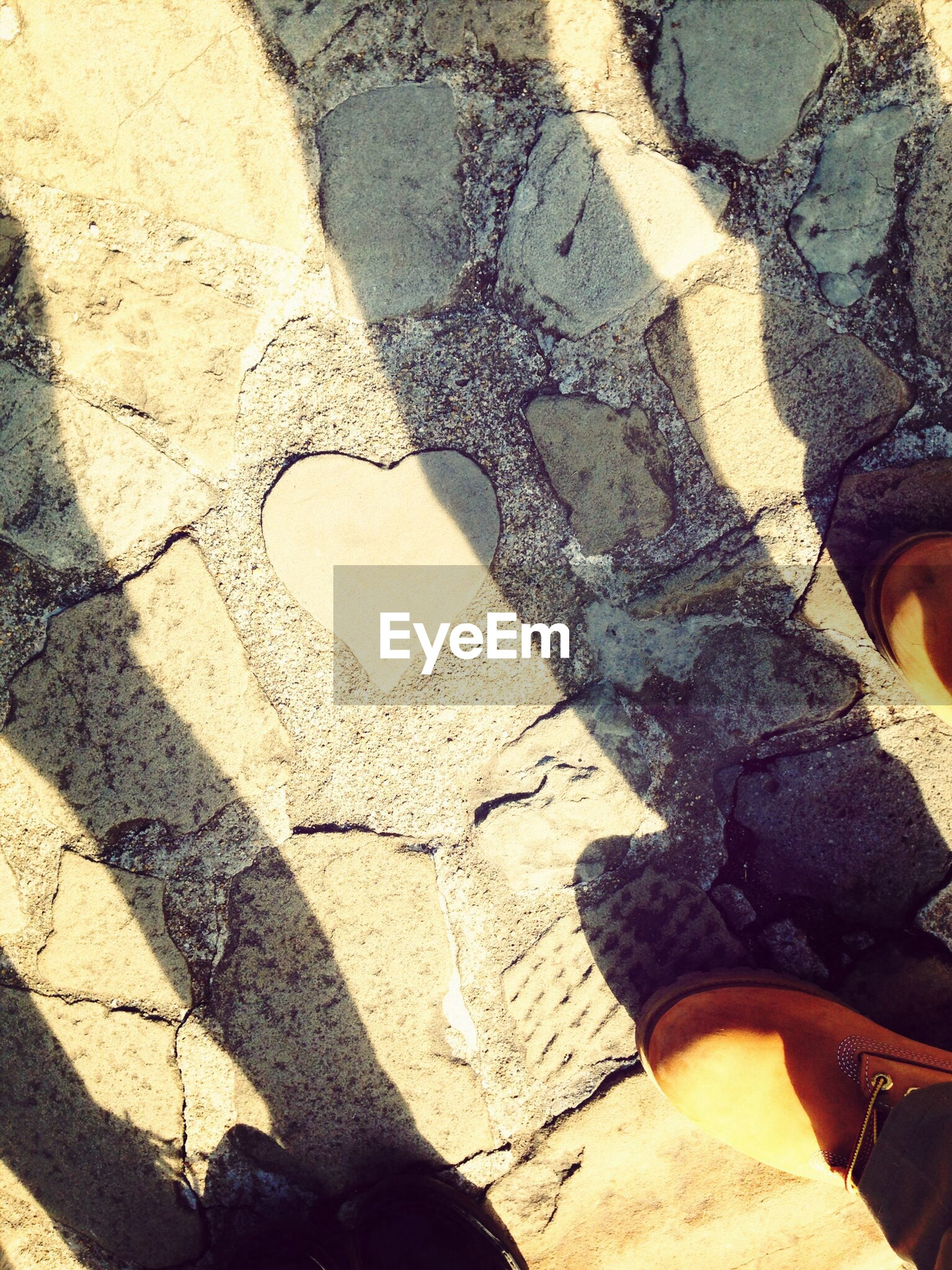 low section, person, lifestyles, shoe, leisure activity, high angle view, personal perspective, standing, human foot, shadow, footwear, men, sunlight, street, unrecognizable person, outdoors