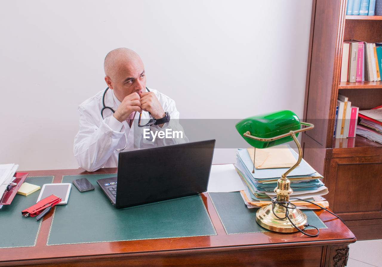 High angle view of doctor sitting with laptop at table in office