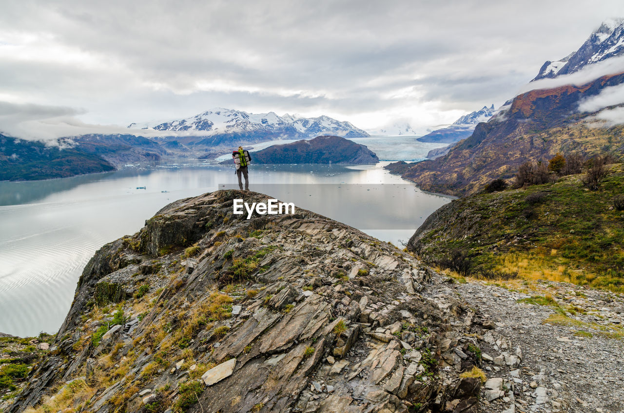 Mid Distance View Of Hiker Standing On Cliff By Lake Against Cloudy Sky