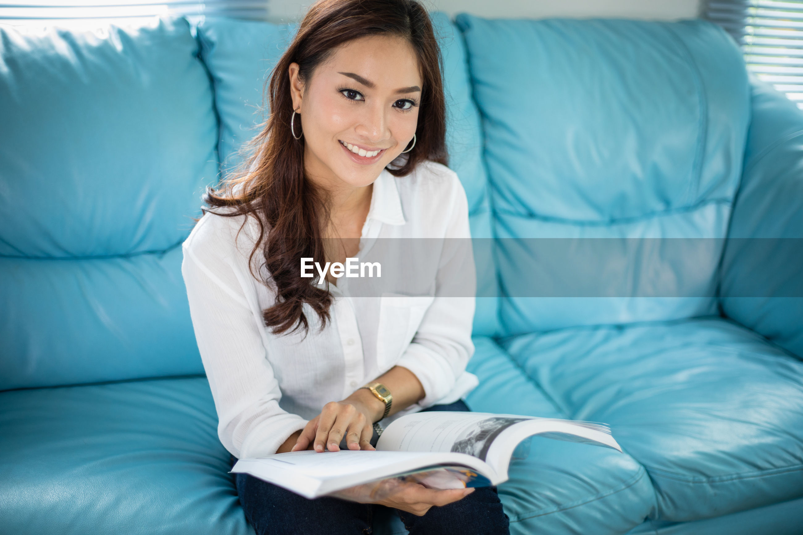 Asian women smiling and reading a book for relaxation on sofa at home