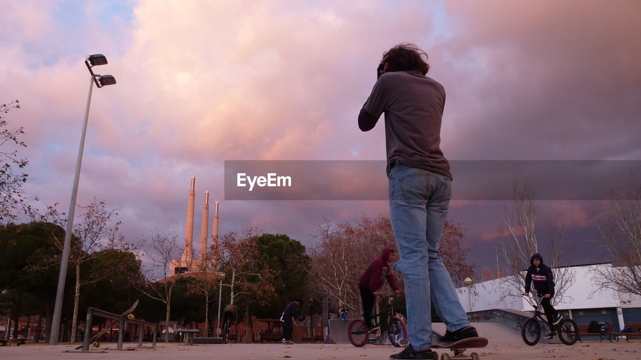 real people, cloud - sky, sky, men, rear view, sunset, casual clothing, transportation, leisure activity, outdoors, lifestyles, one person, tree, nature, day, people