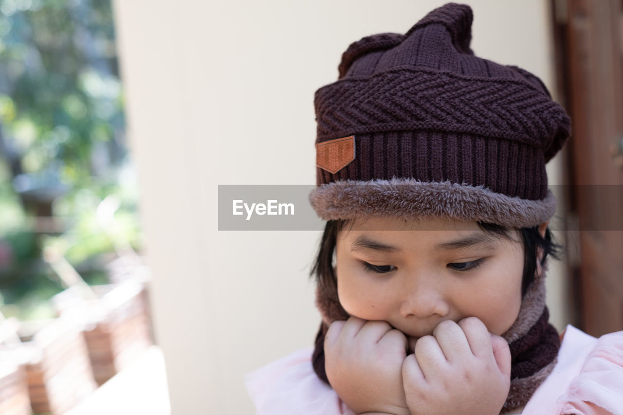Portrait of a cute little girl in wool hat on blurred background