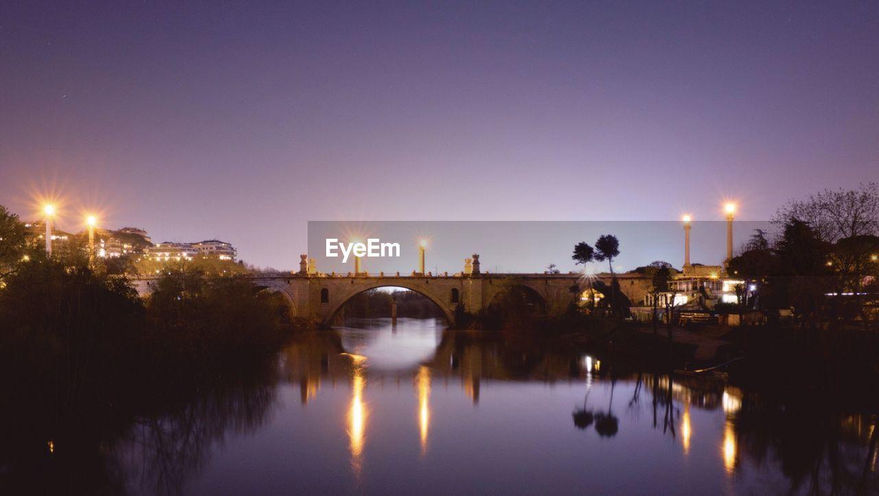 Reflection Of Illuminated Bridge In Water At Night