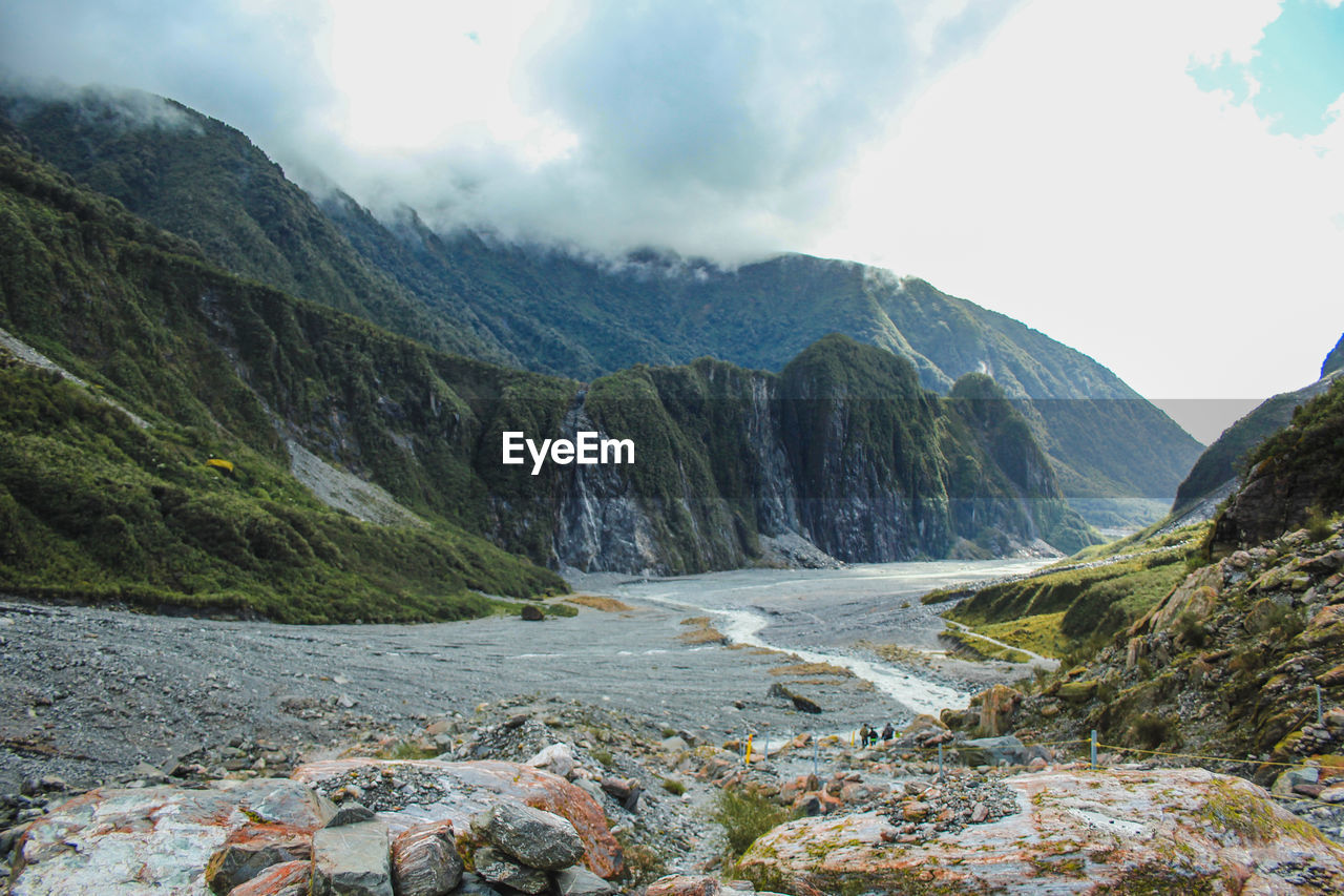 Scenic view of river flowing amidst mountains against sky