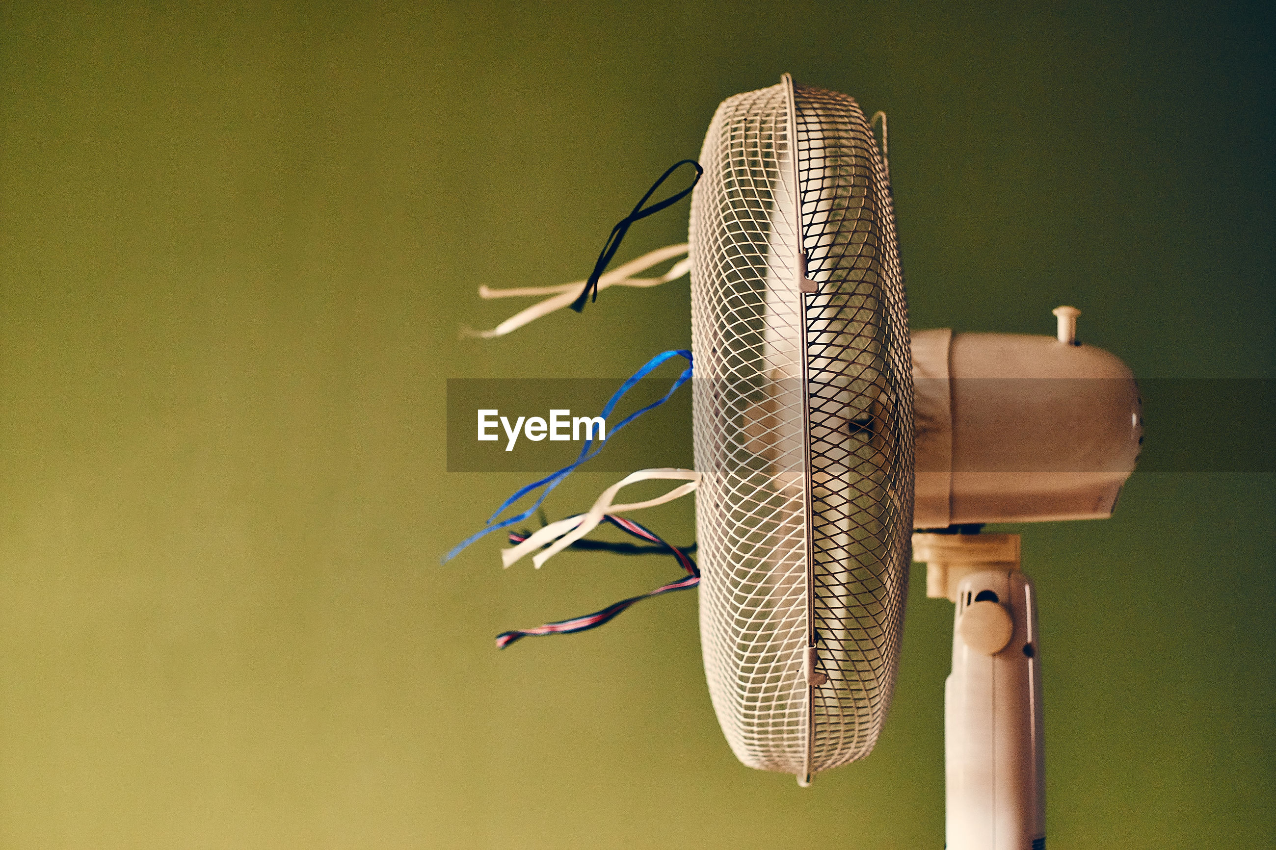 Close-up of electric fan against green wall