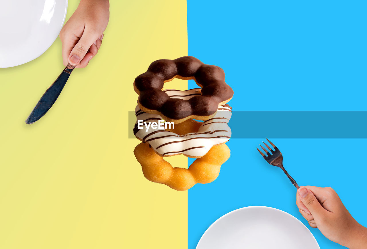 human hand, hand, one person, human body part, holding, indoors, colored background, studio shot, yellow, food, real people, food and drink, finger, unrecognizable person, body part, human finger, lifestyles, kitchen utensil, copy space